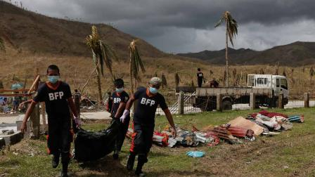 Firemen carry the body of a Typhoon Haiyan victim to a mass grave outside of the city of Tacloban on Thursday Nov. 14, 2013.