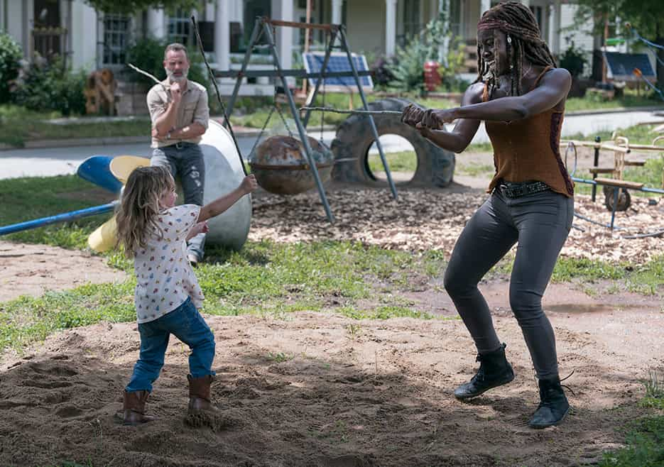 Michonne playing with Judith Grimes while Rick watches from the background (Image Credits: Jackson Lee Davis / AMC)
