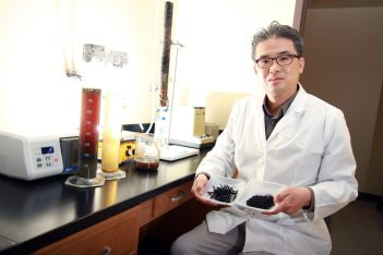 man in lab coat sitting with samples of biocharred dairy manure and dairy hay