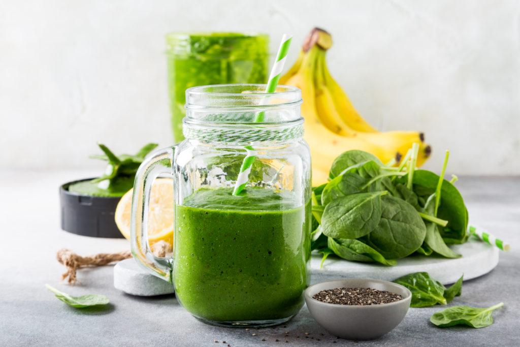 Batido verde saudável com as sementes dos espinafres, da banana, do limão, da maçã e do chia no frasco de vidro e nos ingredientes.  Desintoxicação, dieta saudável, conceito de comida vegetariana.