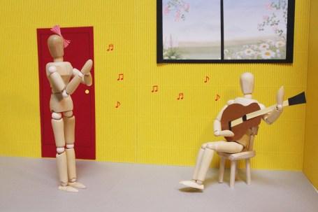 デッサン人形のカップルがギターを楽しんで聞いている