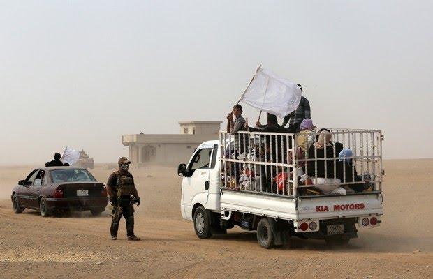 Civis passam por Tob Zawa, a 9 km de Mossul, durante ofensiva expulsar o EI (Foto: Khalid Mohammed/AP)