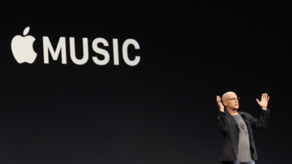 A man speaks on a stage in front of a giant Apple Music logo.