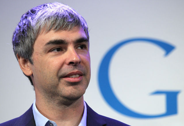 A man in an open-collar suit stands in front of a Google logo.