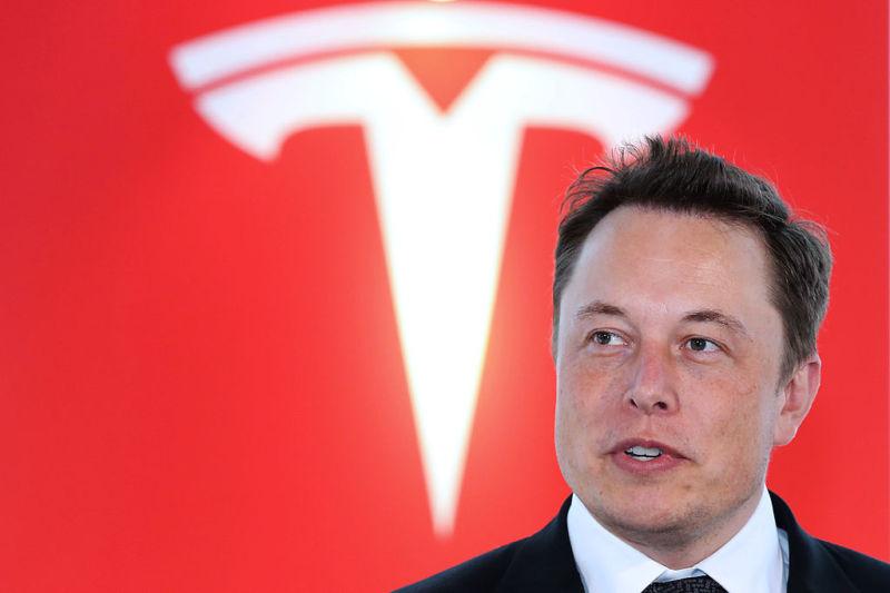 Elon Musk speaks in front of a giant Tesla logo.