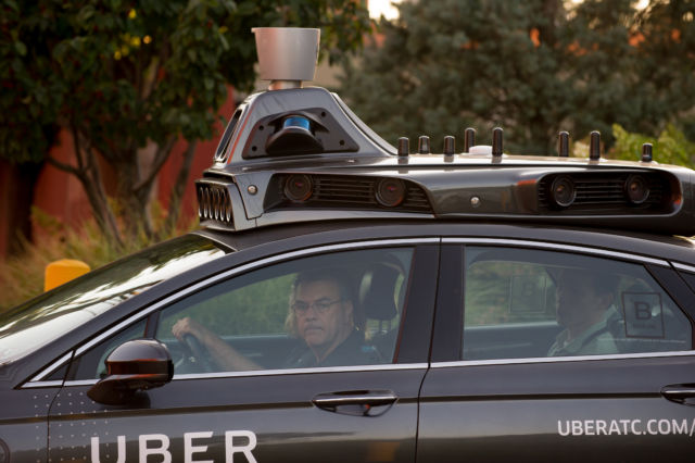An Uber driverless Ford Fusion drives in Pittsburgh, Pennsylvania, with a spinning lidar on top.