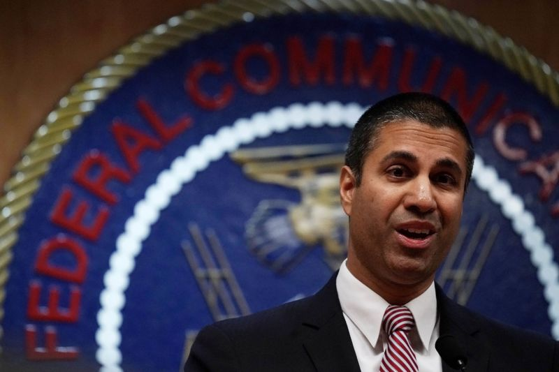 FCC Chairman Ajit Pai standing in front of the FCC seal and speaking to reporters.