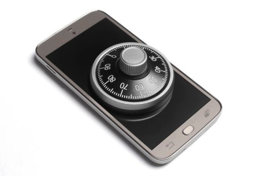 A combination lock sitting on top of a smartphone.