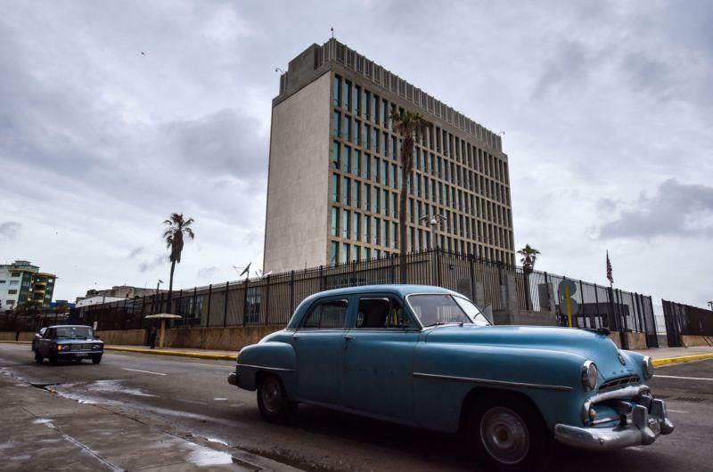 1950s cars driving past a Brutalist, multistory concrete building is peak Cuba.