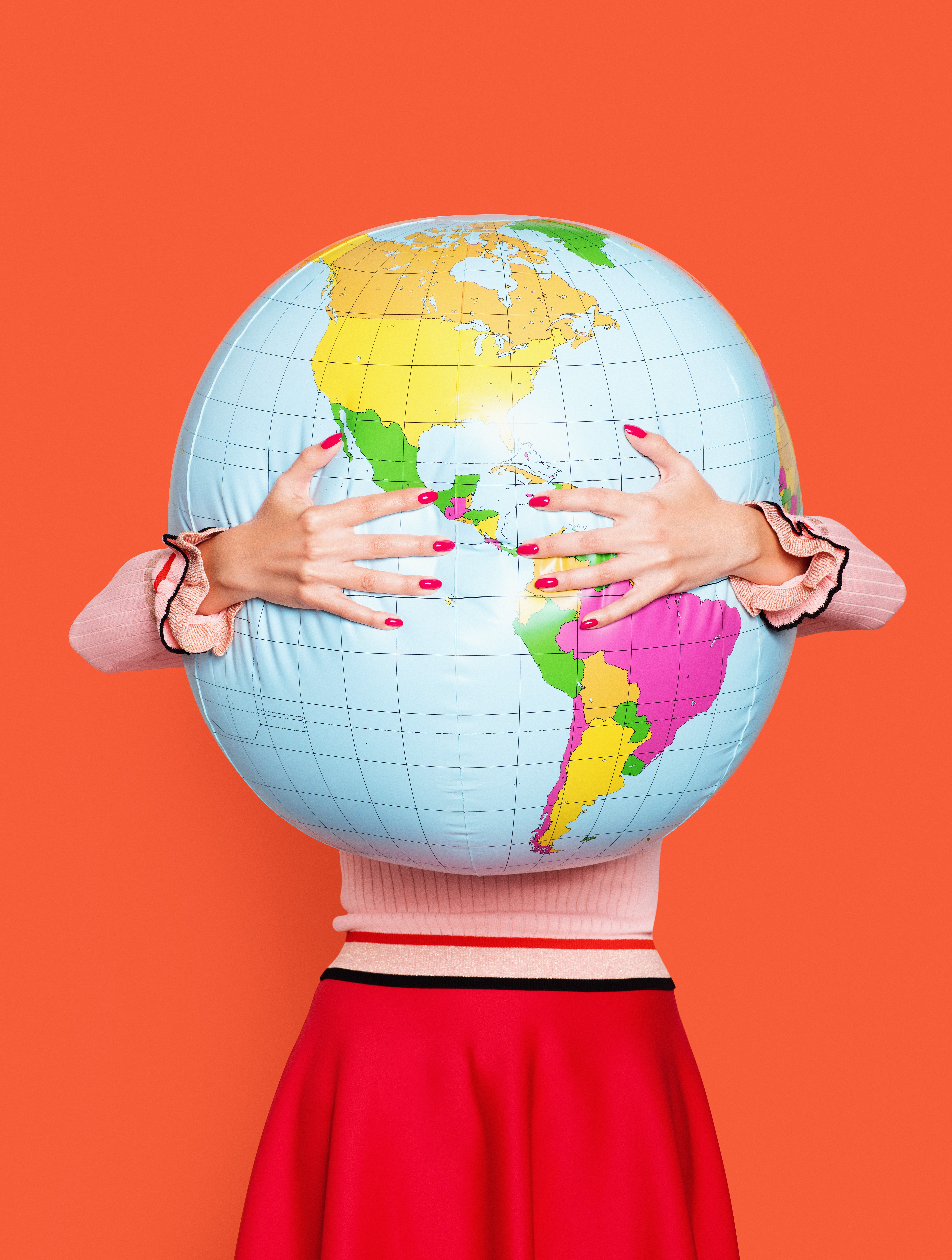 Large inflatable globe getting hugged by a woman in a red skirt.