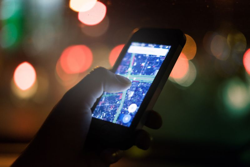 A person's hand holding a smartphone that is displaying a map.