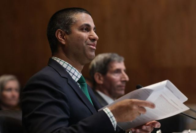FCC Chairman Ajit Pai holding a stack of papers while testifying in front of a Senate committee.