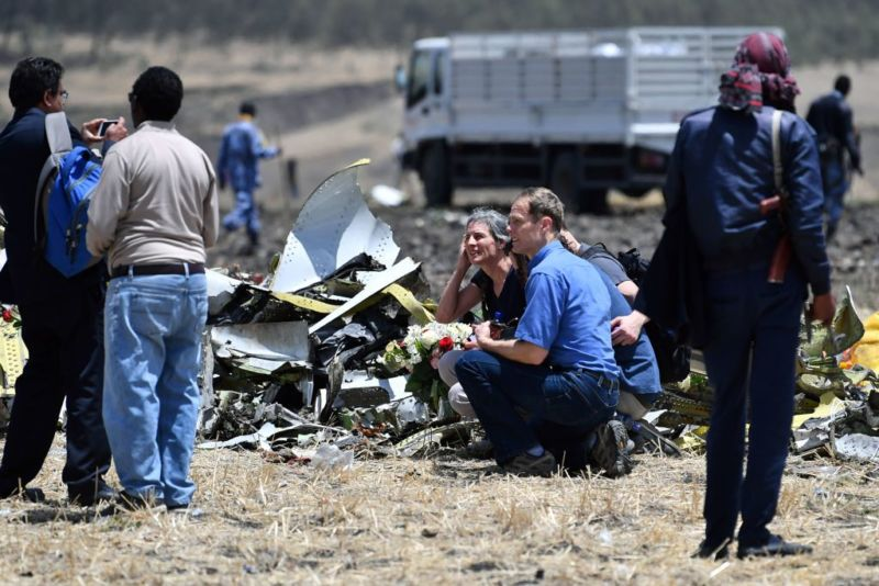 Relatives of the victims of the Sunday plane crash take a picture next to a pile of airplane fuselage at the crash site of the Ethiopian Airlines operated Boeing 737 MAX aircraft, at Hama Quntushele village in the Oromia region, on March 13, 2019. - A Nairobi-bound Ethiopian Airlines Boeing crashed minutes after takeoff from Addis Ababa on March 10, 2019, killing all eight crew and 149 passengers on board, including tourists, business travelers, and