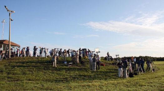 People with cameras and tripods crowd a grassy field, all facing the same direction.