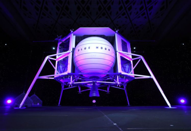 A man on a stage stands in front of full-size model of a spaceship.