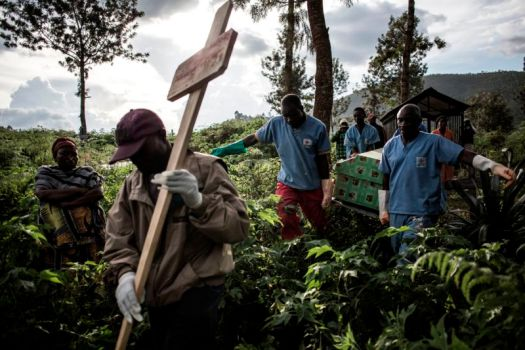 Health workers carry a coffin containing a victim of Ebola virus on May 16, 2019, in Butembo, DRC, a city at the epicenter of the Ebola crisis.