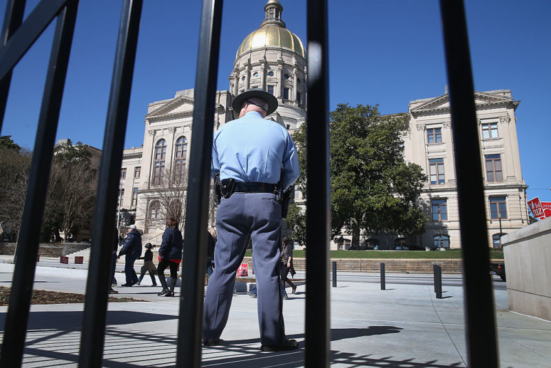 A uniformed police officer stands outside a courthouse with a rotunda.