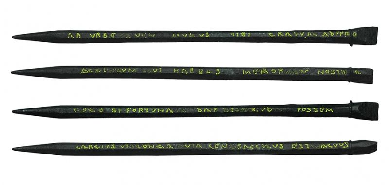 Photo of 4 sides of an iron stylus with text inscribed