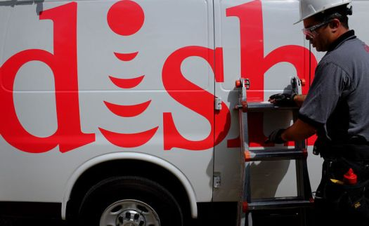 A technician in a hard hat stands next to a Dish Network service vehicle.