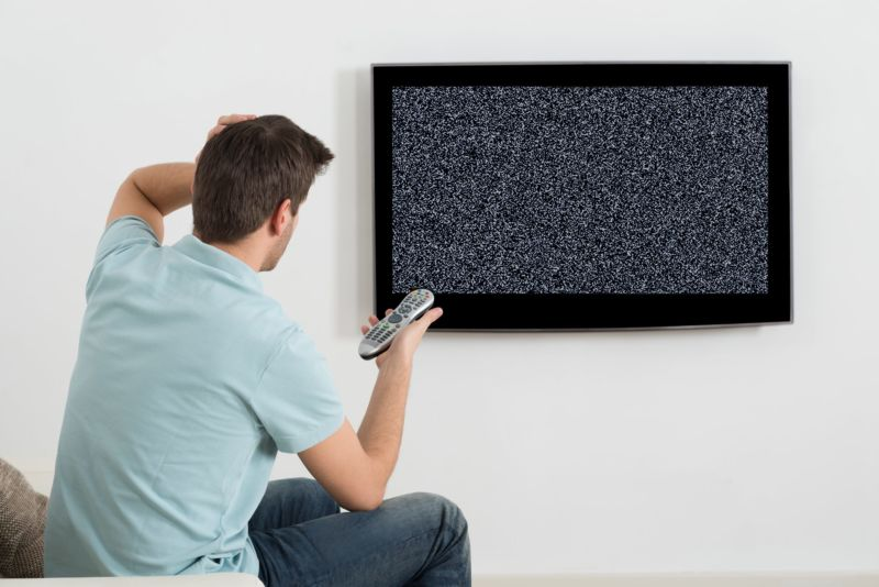A man sitting in front of a TV that shows only static.