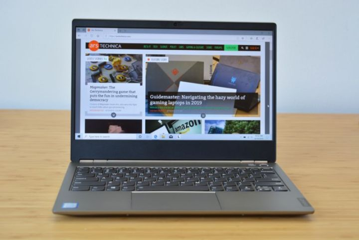 The Lenovo Thinkbook 13 laptop on a wooden table.
