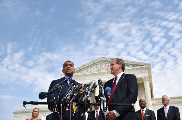 Two men stand in front of an array of microphones before a Federal-style federal building.