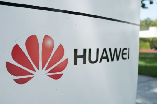 An outdoor sign with Huawei's company name and logo.