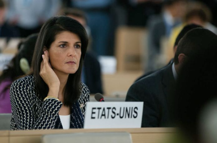 A serious woman listens intently to an earpiece.
