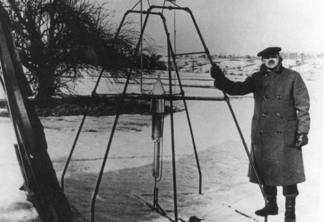 """Robert H. Goddard, bundled against the cold weather of March 16, 1926, holds the launching frame of his most notable invention — the first liquid-fueled rocket, an example of a """"P-type"""" loonshot."""