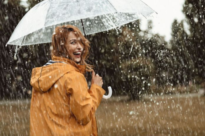 Menina bonita alegre que guarda o guarda-chuva ao passear fora.