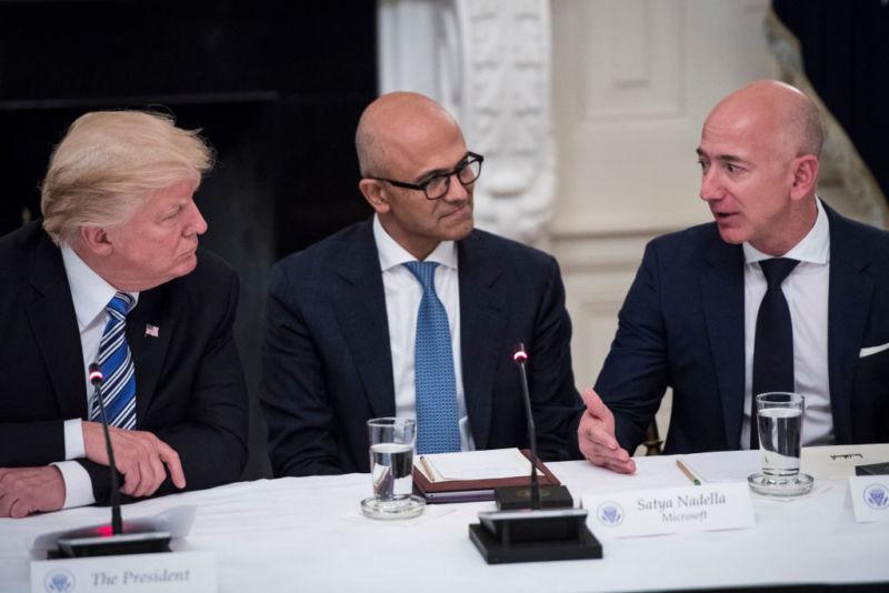 President Donald Trump, Microsoft CEO Satya Nadella, and Amazon CEO Jeff Bezos sit at a table and talk.