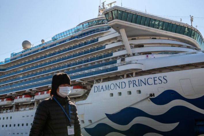A person wearing a face make walks along a port on a sunny day with the Princess Diamond cruise ship docked in the background.