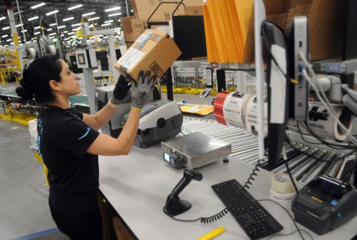 A uniformed woman lifts a small parcel.