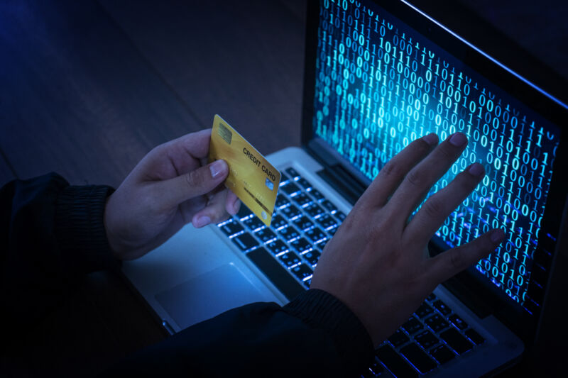 Stock photo of hands operating a laptop while holding a credit card.