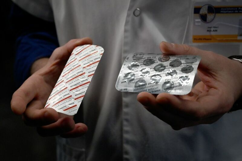 Image of a person's hands holding pill packaging.
