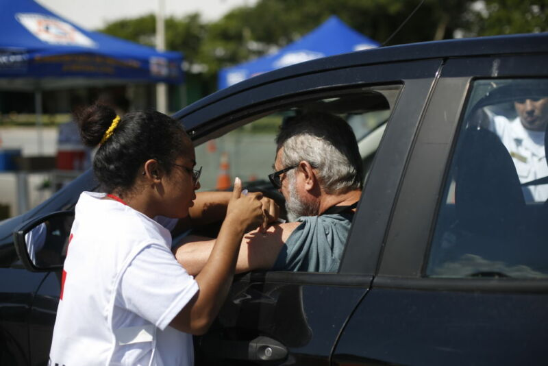 Image of a vaccine being administered to someone in a car.