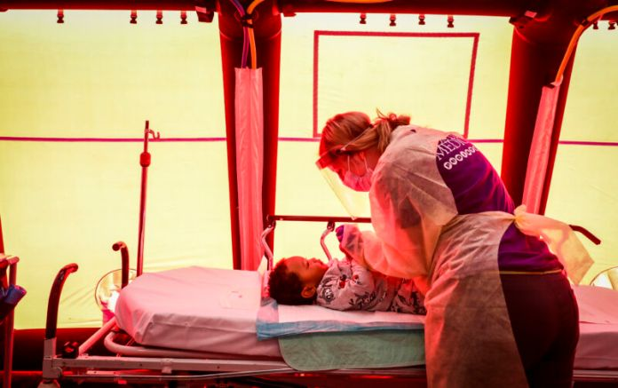 A woman in protective gear looks at a child in a bed.