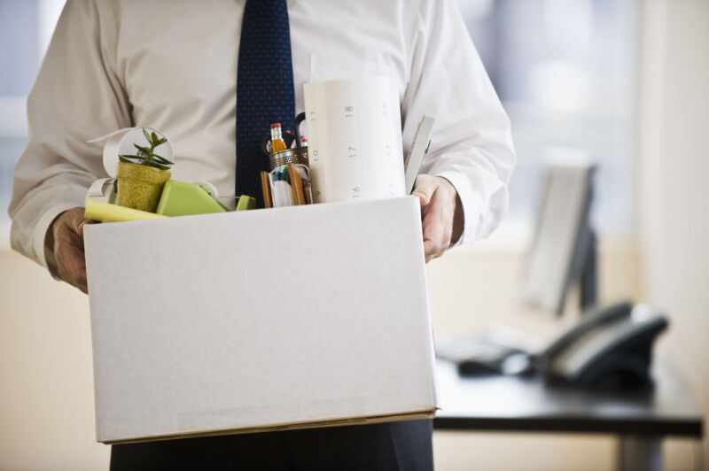A man in an office walks away from his desk carrying a box of knickknacks.