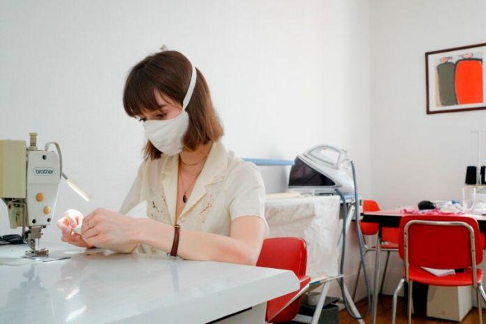 A masked woman operates a sewing machine.