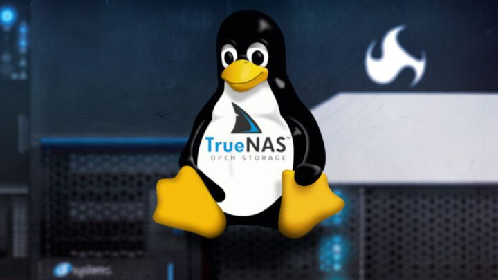 A toy penguin sits atop a computer.