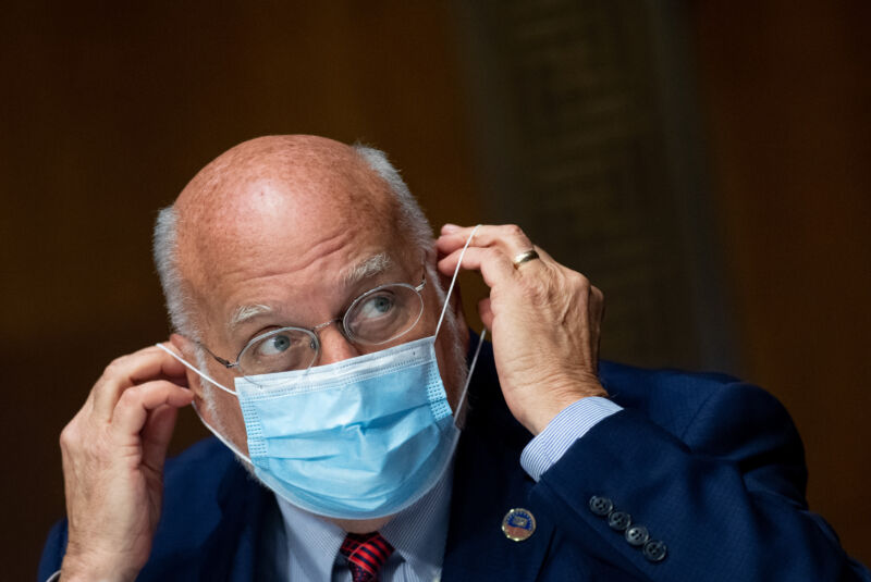 A serious man in a business suit puts on a surgical mask.