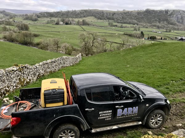B4RN vehicle parked in a field in rural northwest England during a fiber installation.