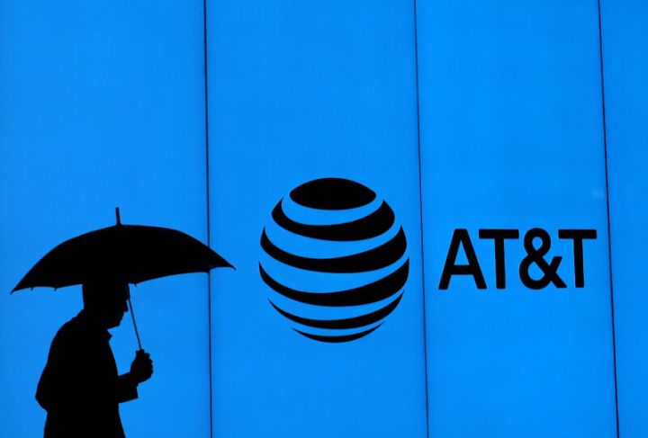 A man with an umbrella walking past a building with an AT&T logo.