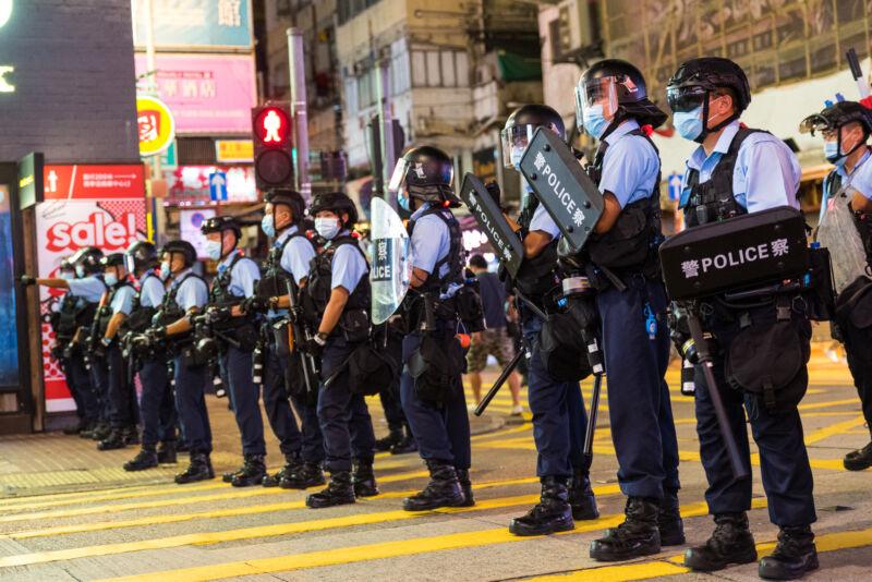 Police in riot gear crowd an urban crosswalk.