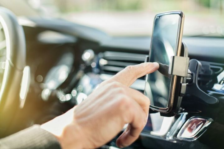 A man's hand tapping a smartphone in a car.