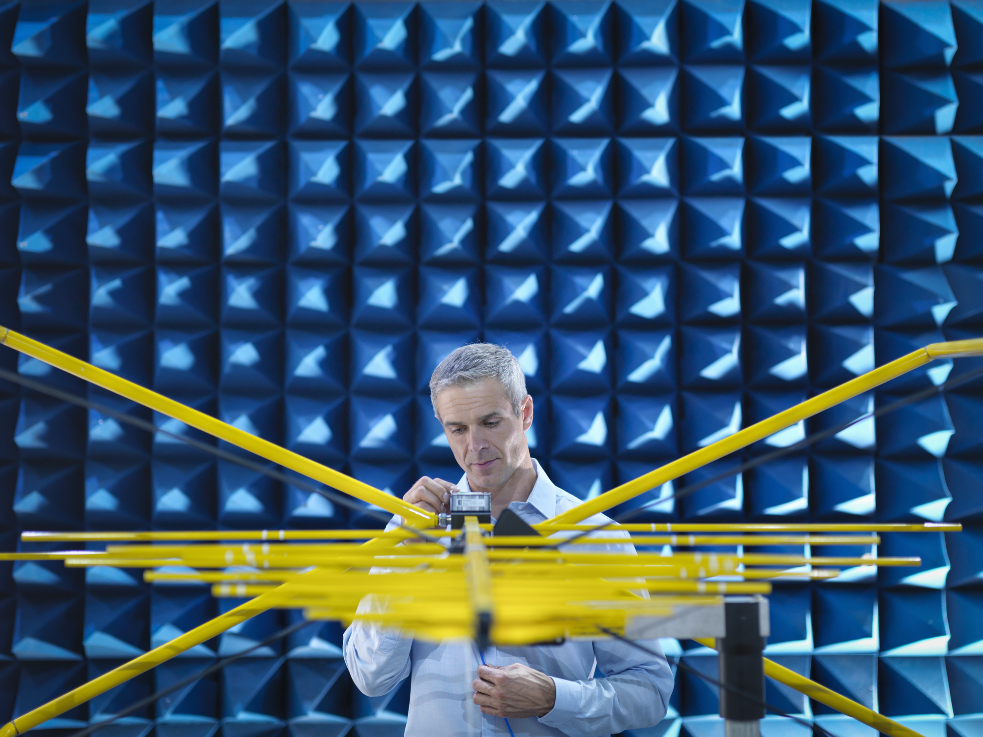 This person is doing electromagnetic testing in a special test chamber, similar to what National Instruments would use to test devices.