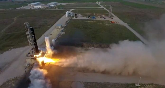 Wide-angle view of a rocket liftoff from a grassy field.