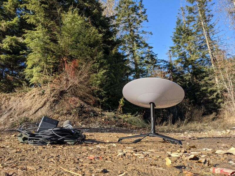 A satellite dish sitting in a forest next to a portable power supply.