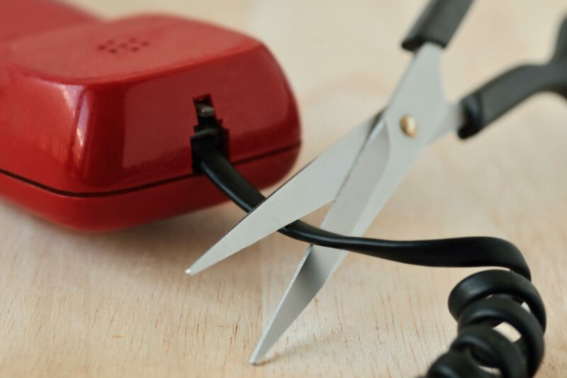 A pair of scissors being used to cut a wire coming out of a landline telephone.