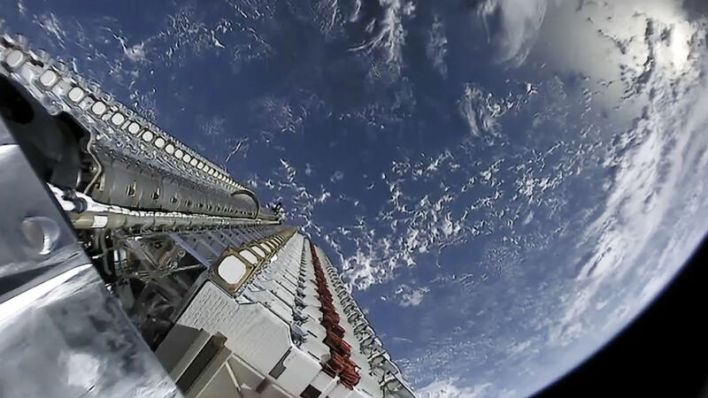 A stack of 60 Starlink satellites being launched into space, with Earth in the background.